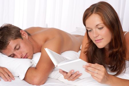 Young couple lying down in bed, woman reading book photo