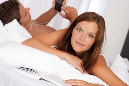Young couple lying down in bed with book and mp3 player photo