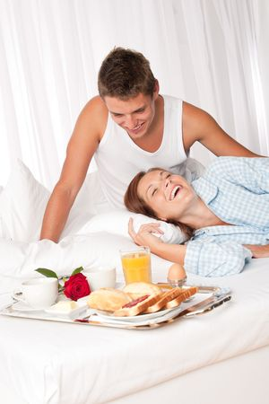 Young smiling couple having luxury breakfast in hotel room photo
