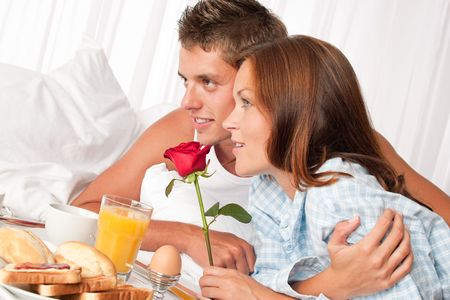 Young happy couple having luxury hotel breakfast photo