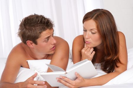 Young man and woman lying down on white sofa, woman reading book photo
