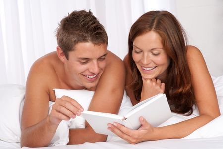Young man and woman lying down on white sofa, woman reading book Stock Photo - 5417561