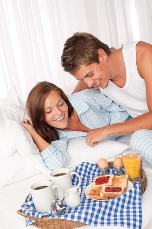 Young man and woman having breakfast together in white bed photo