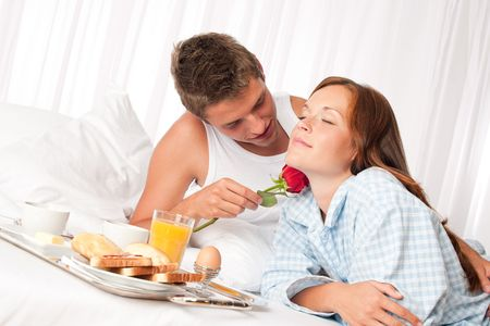 luxury bed: Happy man and woman having luxury hotel breakfast in bed together