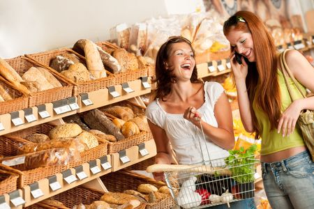 Grocery store: Two women having fun while shopping photo