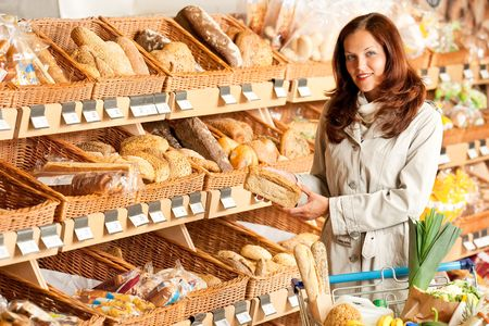 Grocery store: Young woman choosing bread in a supermarket photo
