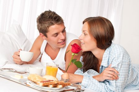 Happy man and woman having luxury hotel breakfast in bed together photo