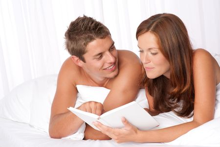 Young man and woman lying down on white sofa, woman reading book Stock Photo - 5428017