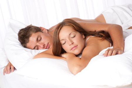 Young man and woman lying down in white bed and sleeping photo