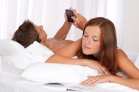 Young couple lying down in bed, woman reading book, man listening to music photo