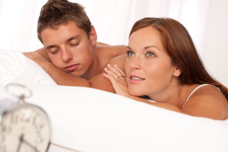 Young couple lying in white bed with silver alarm clock photo