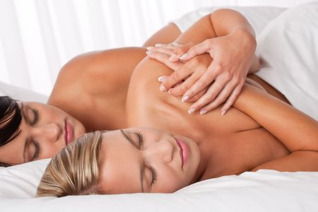 Two young women lying down in white bed and sleeping together naked Stock Photo - 5437651