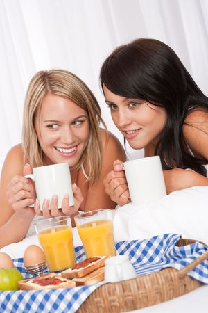 Two young women having breakfast in white bed drinking coffee photo