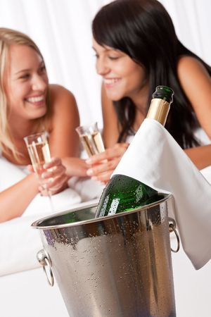 Two smiling women drinking champagne in luxury hotel room, focus on bottle photo