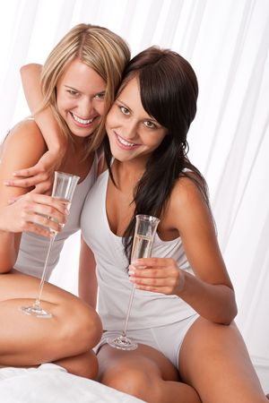 Two women having fun in luxury hotel room and drinking champagne photo