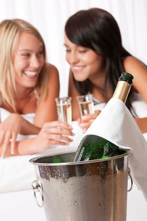 Two young women toasting with champagne  in luxury hotel room Stock Photo - 5479842