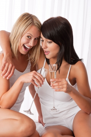 Lesbian couple having fun together, drinking champagne photo