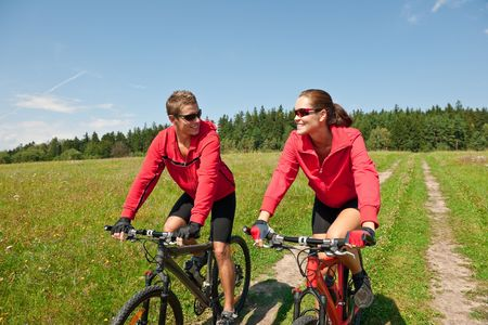 Happy man and woman riding mountain bike in meadow photo
