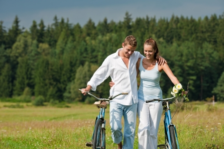 Romantic couple walking in meadow with old bike photo