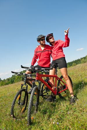 Sportive couple riding mountain bike in meadow on a sunny day photo