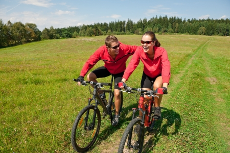 mtb: Sportive couple riding mountain bike in meadow on a sunny day
