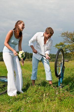 Young man repairing old bike in a meadow photo