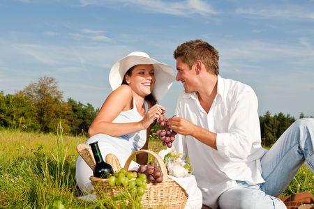 Smiling woman and man eating grapes while having picnic