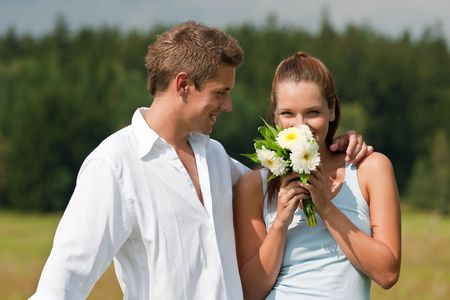 Romantic portrait of young couple  with aster flowers on a sunny day Stock Photo - 5509556