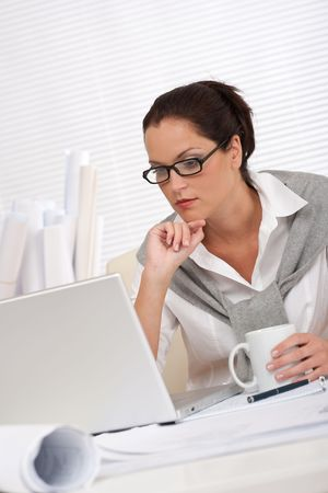female architect: Female architect with laptop and coffee sitting at the office
