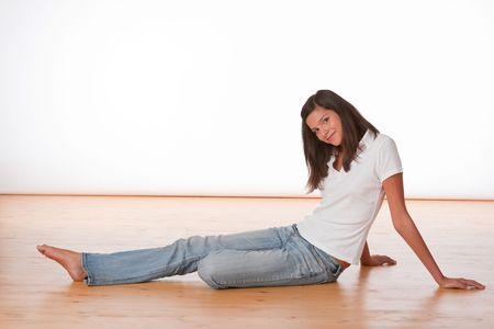 long shot: Long Shot di adolescente felice seduta sul pavimento di legno Archivio Fotografico