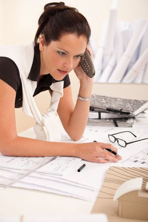 Female architect busy at the office calling and holding pen Stock Photo