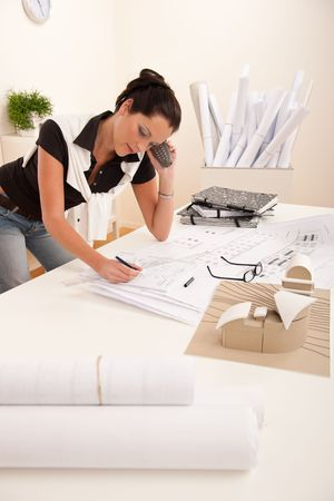 Female architect busy at the office calling and holding pen photo