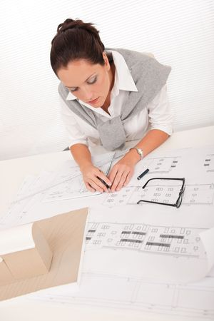 female architect: Attractive female architect watching plans at the office