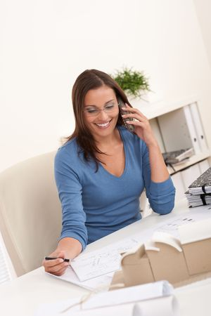 architect office: Young female architect working at office holding phone and pen Stock Photo