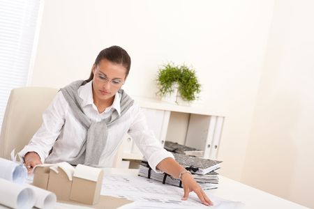 Young female architect working at the office with plans photo