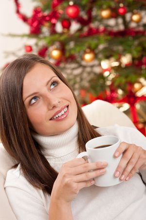 Brown hair woman relaxing with coffee on Christmas in front of Christmas tree photo