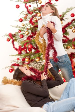 Two young woman having fun with Christmas decoration in front of tree photo