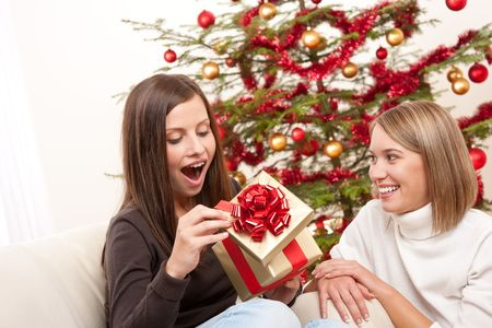 Young woman unpacking Christmas gift surprised photo
