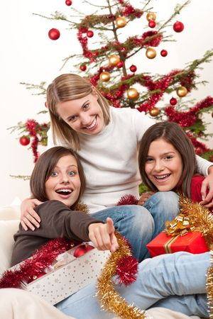 Three young women having fun on Christmas in front of tree photo