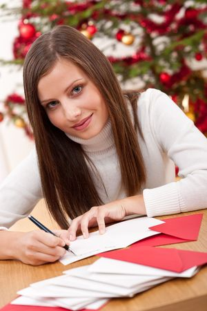 Young woman thinking while writing Christmas card in front of tree photo