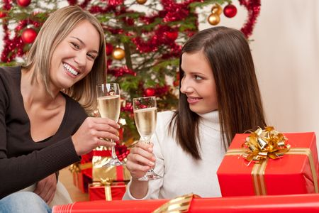 Two young woman with champagne and Christmas tree and present photo