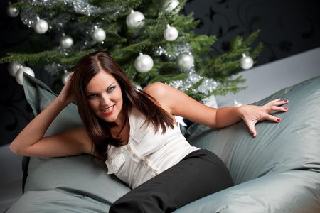 Provocative sexy woman posing in front of silver decorated Christmas tree photo