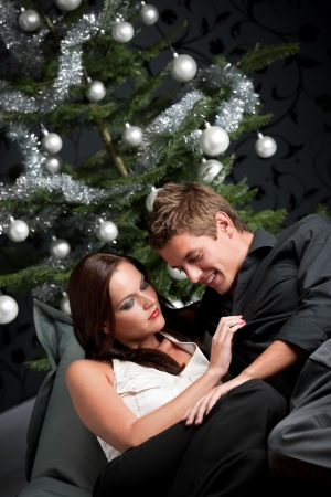 Extravagant man and woman in front of Christmas tree and black wallpaper photo