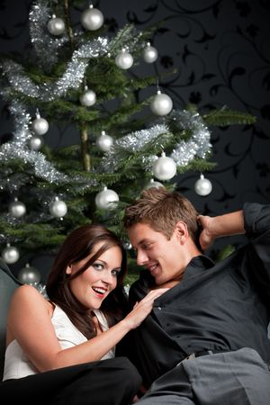 provocative couple: Extravagant man and woman in front of Christmas tree and black wallpaper