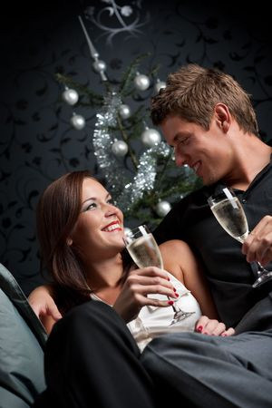 provocative couple: Young extravagant man and woman with champagne sitting in front of silver decorated Christmas tree
