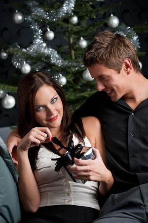 provocative couple: Young sexy couple in front of Christmas tree, woman unpacking present Stock Photo