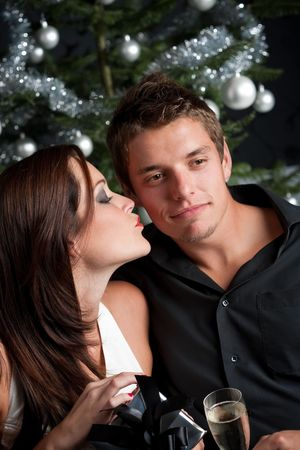 provocative couple: Young sexy couple kissing in front of Christmas tree, woman unpacking present