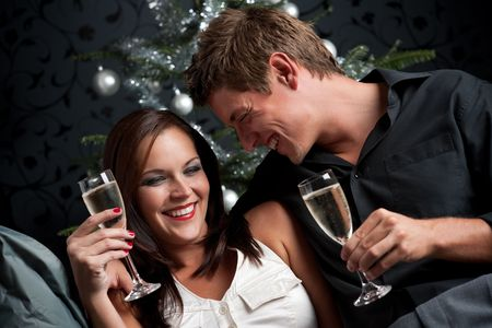 Young extravagant man and woman with champagne sitting in front of silver decorated Christmas tree photo