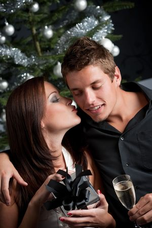 Young sexy couple kissing in front of Christmas tree, woman unpacking present photo