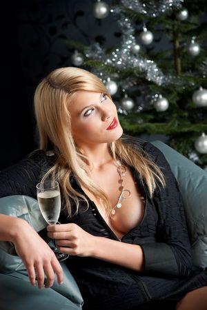 Portrait of blond sexy woman with glass of champagne on Christmas photo